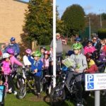 Photograph of people on bikes awaiting start