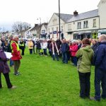 Photograph of people gathering on the village green awaiting the start of the walk