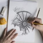 Photograph of pit wheel in a pencil drawing with artists hands