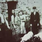 Old photo of a group of people and pig