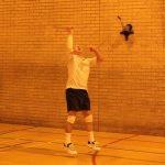 Photograph of knee strapped man playing badmington