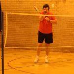 Photograph of red shirted man playing badmington