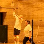 Photograph of people playing badmington with man volleying