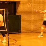 Photograph of man in action playing badmington with one at net and one in background