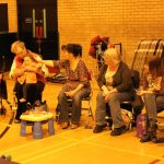 Photograph of mothers talking with carers and toddlers enjoying play
