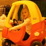 Photograph of child in toy car