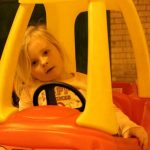 Photograph of child in toy car head on side