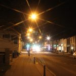 Photograph of car headlights on front street