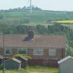 Photo of rooftops and wind turbine