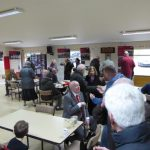 Photograph of people in community centre taking and having refreshments
