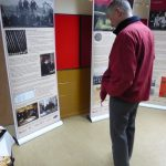 Photograph of man looking at exhibition bords at Community Centre