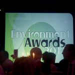 Photograph of Environmental awards prentation slide with sillouettes in forground