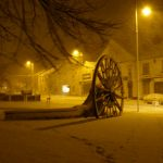 Photograph of pit wheel in the snow with branches in foreground