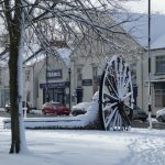 Photograph of pit wheel in the snow from distance trees included