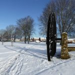 Photograph of pit wheel in the snow this time with a massive long shadow