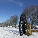Photograph of pit wheel in the snow with great blue skies