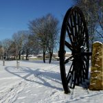 Photograph of pit wheel in the snow with a rather large shadow