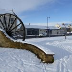 Photograph of pit wheel and the wall that is part of the structure in the snow