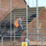 Photograph of builder on roof