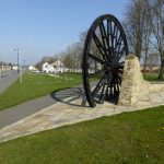 Photograph of pit wheel and shadow taking looking north right across village grreen