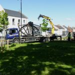 Photograph of pitwheel being taken off lorry by crane