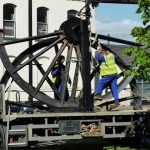 Photograph of pitwheel being taken off lorry by crane WITH MEN ON LORRY