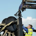 Photograph of pitwheel being taken off lorry by crane WITH MEN WORKING HARD