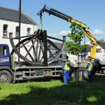 Photograph of pitwheel being taken off lorry by crane STEP 1