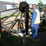 Photograph of pitwheel being lowered to site with man watching