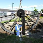 Photograph of pitwheel being fixed to site ith man in foundation