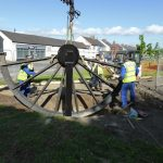 Photograph of pitwheel being fixed to site with two mwn working