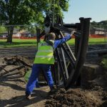 Photograph of pitwheel being fixed to site by workmen