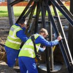 Photograph of pitwheel being fixed to site with men working carefully