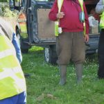 Photograph of pitwheel being fixed to site with man wearing boots