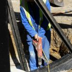 Photograph of pitwheel being fixed to site close up of worker