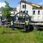 Photograph of second half of pitwheel being lifted from lorry