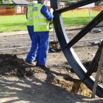 Photograph of second half of pitwheel being fixed to site with mens legs in background