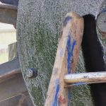 Photograph of second half of pitwheel being fixed to site focussing on centre of wheel