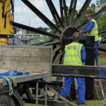 Photograph of second half of pitwheel being fixed to site in closeup with workers its nearly there