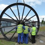 Photograph of second half of pitwheel being fixed to site by three workers