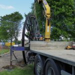 Photograph of second half of pitwheel being fixed to site with lorry in foreground