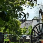 Photograph of second half of pitwheel being fixed to site taken through trees in landscape
