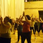 Photograph of Zumba participants with hand held high