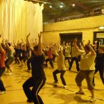 Photograph of Zumba participants bend down arm up