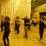 Photograph of Zumba participants with arms out like the hokey cokey