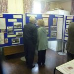Photographs of a couple examining display boards and exhibition materials