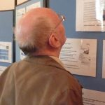 Photographs of man looking at display boards and exhibition materials