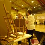 Photograph of ladies from an art group with easels in forground