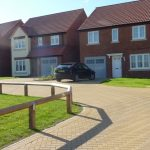 Photograph of more new houses completed with shadow cast by fence