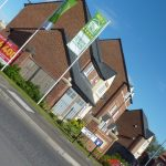 Photograph of more new houses completed taken on an angle complete with flags